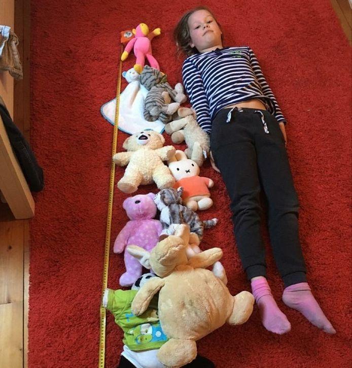 Floor Dassen naast haar uitgemeten rij van anderhalve meter knuffels.