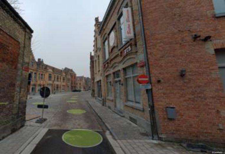 In de straat worden de rioleringsdeksels omhoog gebracht om te kunnen asfalteren
