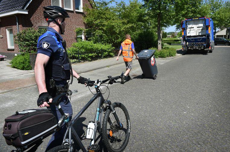 Ad van den Berk, buitengewoon opsporingsambtenaar (boa) van de gemeente Best, terwijl hij op zijn mountainbike achter de vuilniswagen aan fietst. Beeld Marcel van den Bergh
