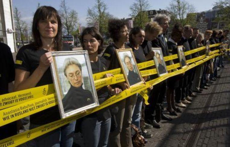 Amnesty International demonstreerde vorige week vrijdag bij het Amsterdamse stadhuis aan de Amstel met foto's van de vermoorde journalist Anna Politkovskaya. ANP Beeld