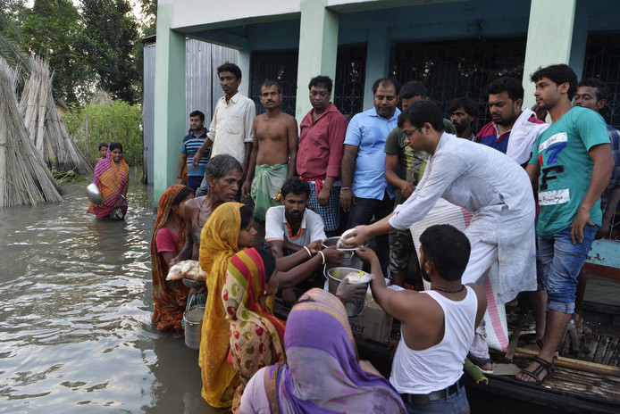 Dorpelingen krijgen voedsel uitgereikt. Veel woningen zijn overstroomd.