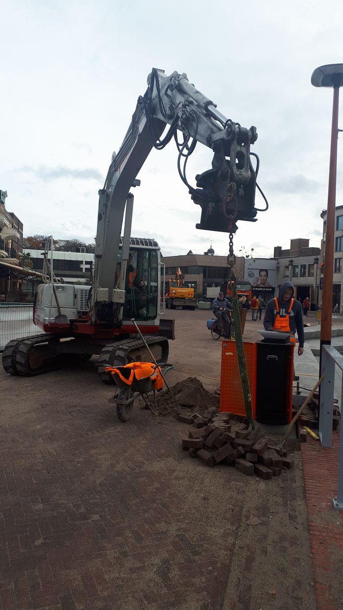 Met behulp van een kraan wordt een van de nieuwe afvalbakken op het Marktplein verankerd.