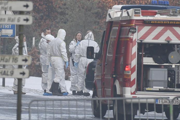 Politierechercheurs en brandweermensen overleggen bij het drugslaboratorium in het Belgische Eksel, waar vorige week drie jonge Brabanders dood werden gevonden.