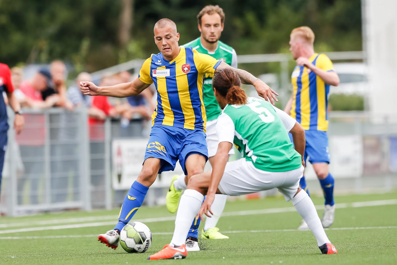 Frenk Keukens (links) voor FC Oss in actie tijdens een oefenduel met FC Dordrecht.