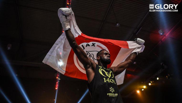 Kickbokser Murthel Groenhart komt op met een vlag van Ajax. Beeld James Law, GLORY Sports International