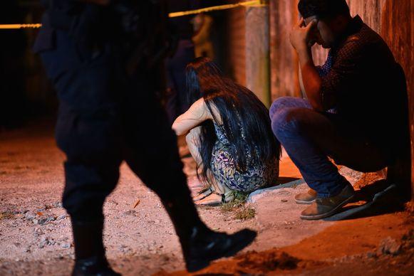 Familieleden zitten aangeslagen buiten het restaurant waar schutters dertien mensen om het leven brachten