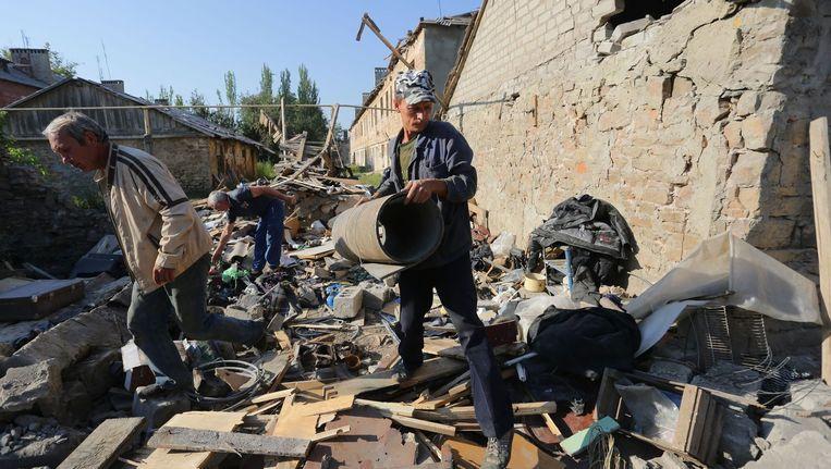 Buurtbewoners ruimen de overblijfselen van hun vernielde huizen op na gevechten tussen het Oekraïense leger en pro-Russische separatisten.