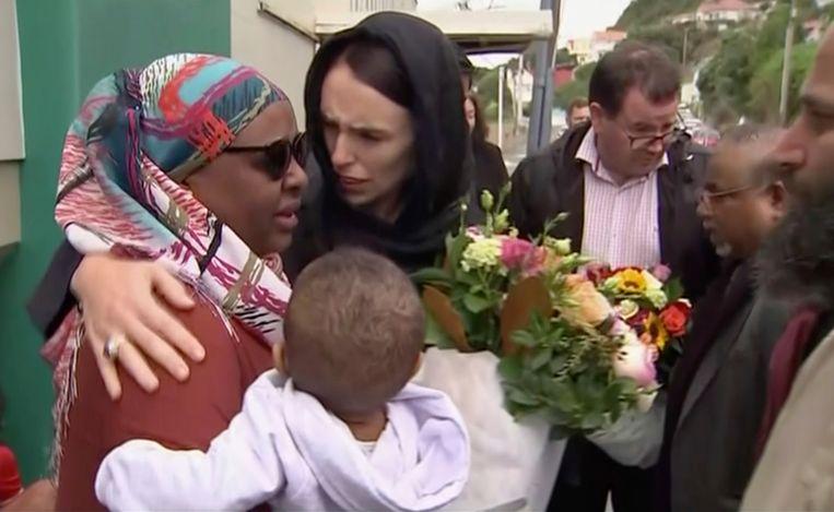 De Nieuw-Zeelandse premier Jacinda Ardern troost een vrouw bij een bezoek aan de Kilbirnie moskee in Wellington, waar bloemen worden neergelegd voor de slachtoffers van de aanslag in Christchurch. Beeld AP