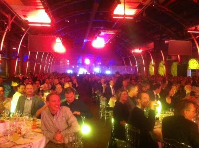 Publiek aan meer dan zestig tafels in de Koepelhal.