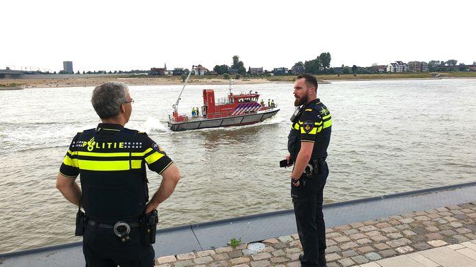 Politieagenten staan bij de Waal te posten en de brandweerboot is onderweg.