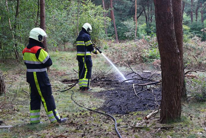Brandweermannen uit Heesch zorgen ervoor dat het vuur niet weer oplaait