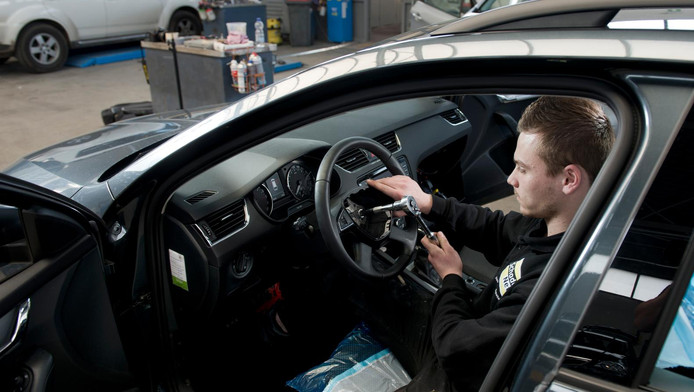 Een monteur in een garage werkt aan het herstel van het stuur na diefstal van de airbag.