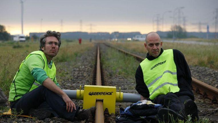 Actievoerders van Greenpeace, vastgeketend aan het spoor waar het kerntransport over zou moeten rijden. © Greenpeace/Beentjes Beeld null