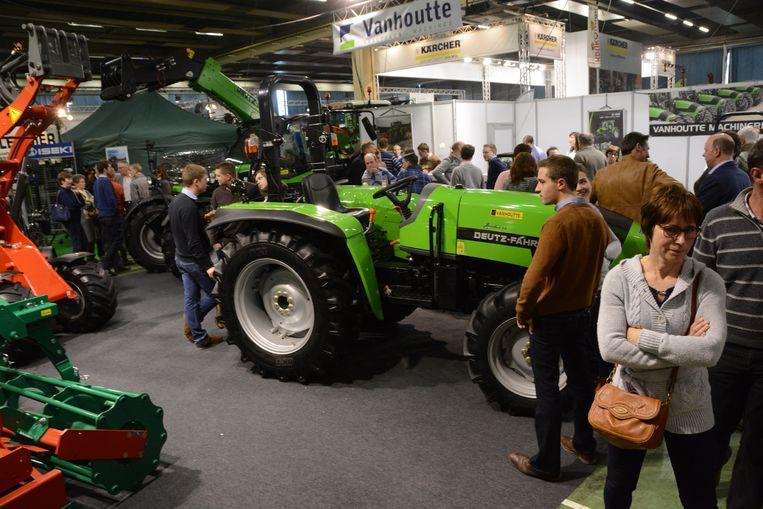 De bezoekers inspecteren enkele landbouwvoertuigen.