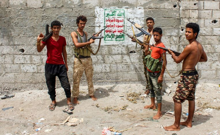 Fighters of the Giant Unit in Hodeida point their guns at Houthi graffiti that reads: 'God is the greatest ... death to America, death to Israel, curseth be the Jews, blesseth be Islam.' Beeld Saleh al Obeidi/AFP