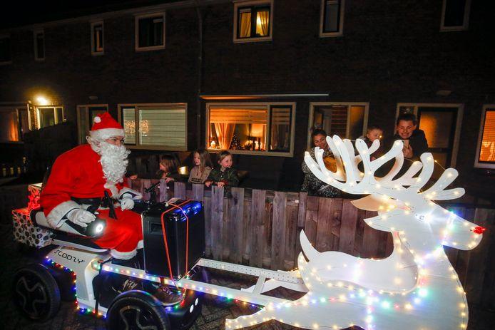 Job van de Kieft rijdt op zijn supersonische arrenslee door het Soesterkwartier terwijl het schoolpersoneel van De Kubus achter hem door een megafoon kinderen en ouders in het Soesterkwartier een zalig Kerstmis wenst.