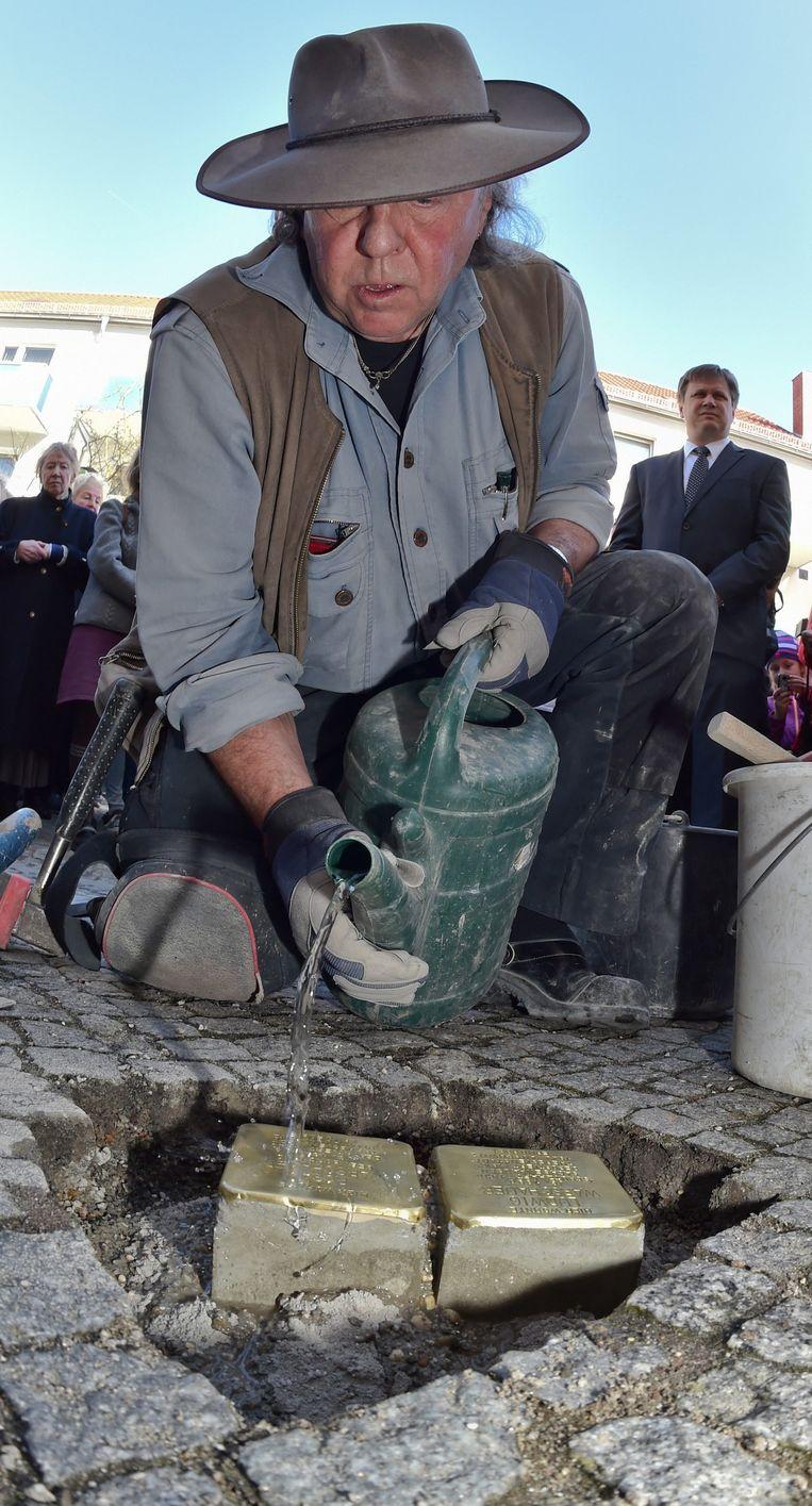 Kunstenaar Gunter Demnig plaatst de Stolpersteine in Beeskow in het oosten van Duitsland, in maart 2014 Beeld anp