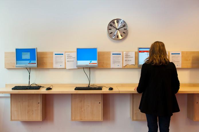 Een jonge vrouw bekijkt vacatures bij het UWV Werkplein in Den Haag.