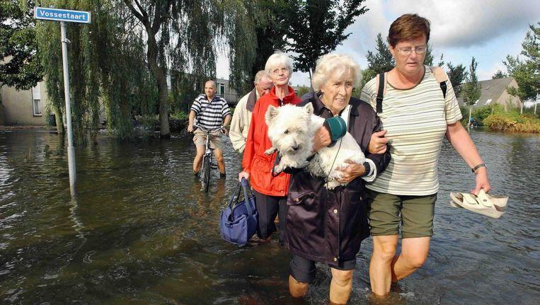 In 2005 overstroomde een wijk in Wilnis doordat een dijk doorbrak. Bewoners verlaten hun huizen. Beeld Raymond Rutting / de Volkskrant