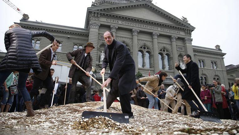 Een muntje voor elke inwoner. Leden van de actiegroep op het Ferale Plein in Bern Beeld epa