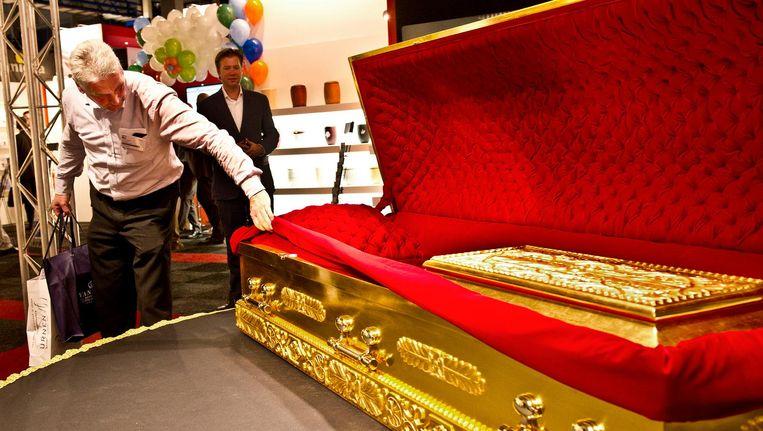 Een met goud belegde kist op de Uitvaart Vakbeurs in Gorinchem. Het is niet verplicht een overledene in een kist te begraven of te cremeren. Beeld anp