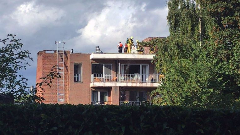 De brandweermannen op het dak van het appartementsgebouw.
