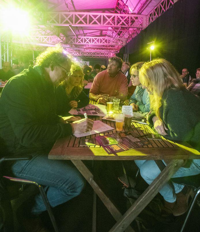 Deelnemers bespreken de pittige vragen tijdens een eerdere editie van de PopquizXL.