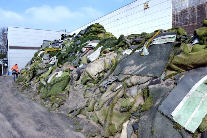 De stapels kunstgras op het terrein van Tuf Recycling zijn hoger dan de toegestane vier meter. Grasmatten die rubbergranulaat bevatten, moeten zijn afgedekt om te voorkomen dat het rubbergranulaat zich verspreidt door wind of water.