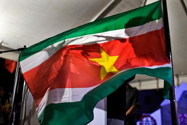 Bij de herdenking van de coup die in 1980 plaatshad, wappert de vlag van Suriname met daarin het silhouet van Desi Bouterse.