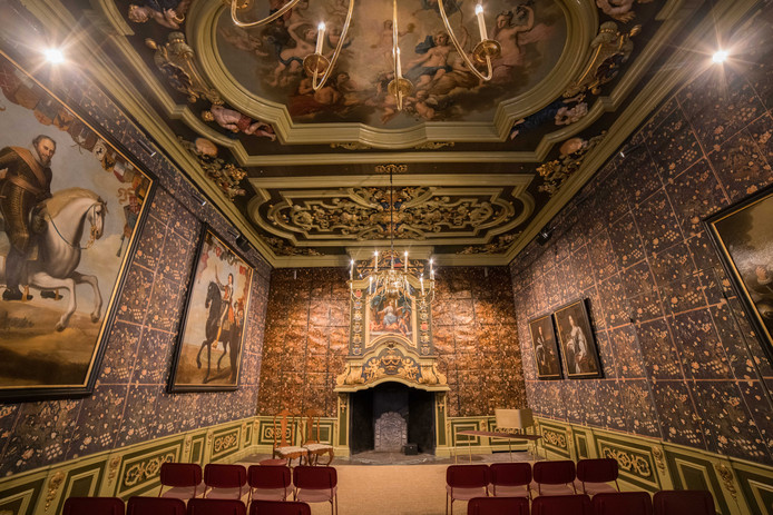 De gerestaureerde raadzaal met links de portretten van Willem van Oranje en Maurits. Vanwege het zeer zeldzame goudleerbehang draagt het boek over het Oude Stadhuis de titel 'Het gouden hart van de stad'.