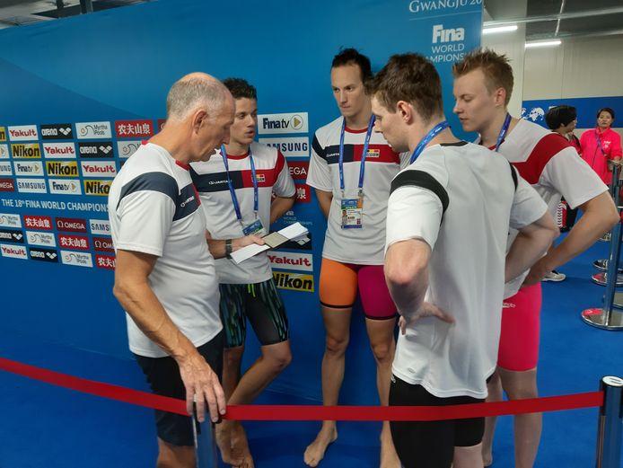 Coach Gaastra houdt na de aflossing een debriefing met zijn zwemmers.