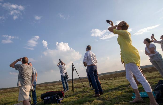 Wwethouder Leon Meijer en andere belangstellenden horen de Belevingsvlucht overkomen op de Ginkelse Heide.