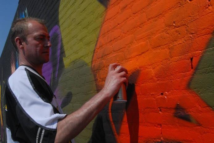 Graffitischrijver Mike Scholten(39) uit Zoetermeer is bezig met het taggen van zijn artiestennaam.
