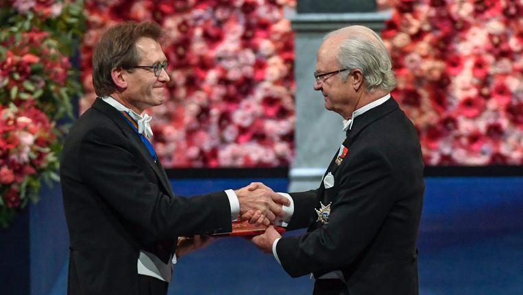 Ben Feringa (links) ontvangt de Nobelprijs uit handen van Koning Carl Gustaf van Zweden. Beeld EPA