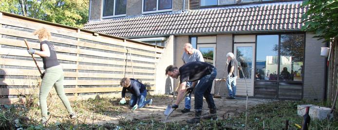 Vrijwilligers knappen een tuin op.