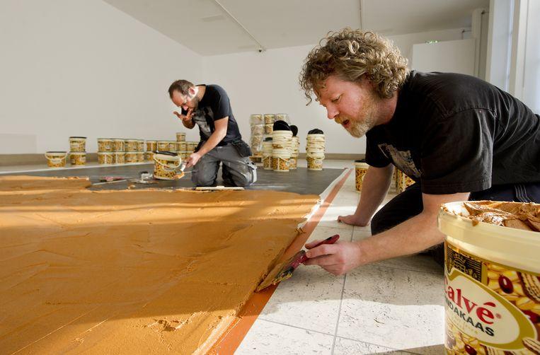 De vloer in het Rotterdamse Boijmans van Beuningen wordt besmeerd met pindakaas. Beeld ANP