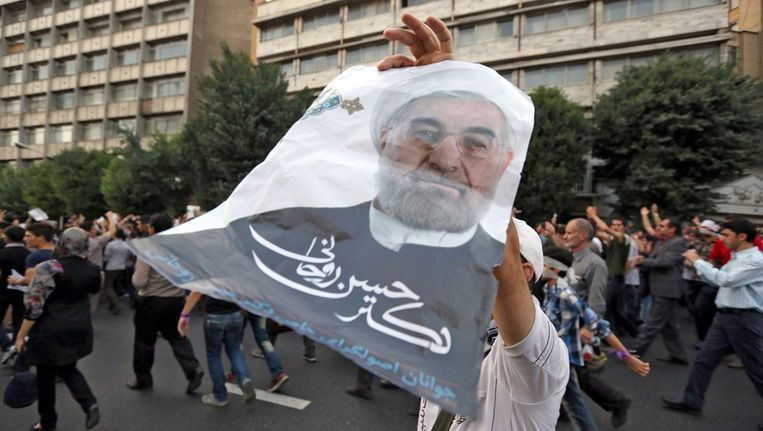 Supporters van Rohani vieren zijn overwinning op straat in Teheran. Beeld epa