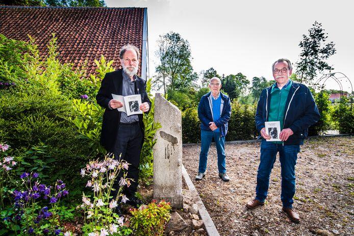 Bert Smeenk (links) met het boekje over Piet Sloot bij het zuiltje dat ooit op het graf van de gesneuvelde Eibergse soldaat stond  Naast hem de broers Peter (midden) en Geert Sloot, voor wie Piet oom had moeten zijn.