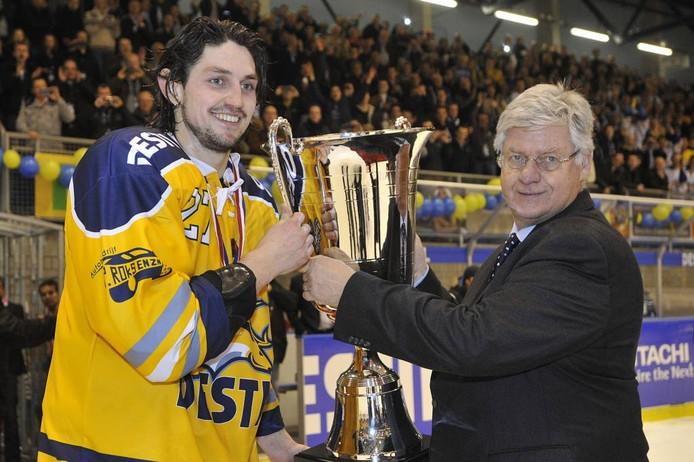 Ruud Vreeman, voorzitter van de Nederlandse IJshockey Bond, reikt de beker uit aan Hagemeijer.