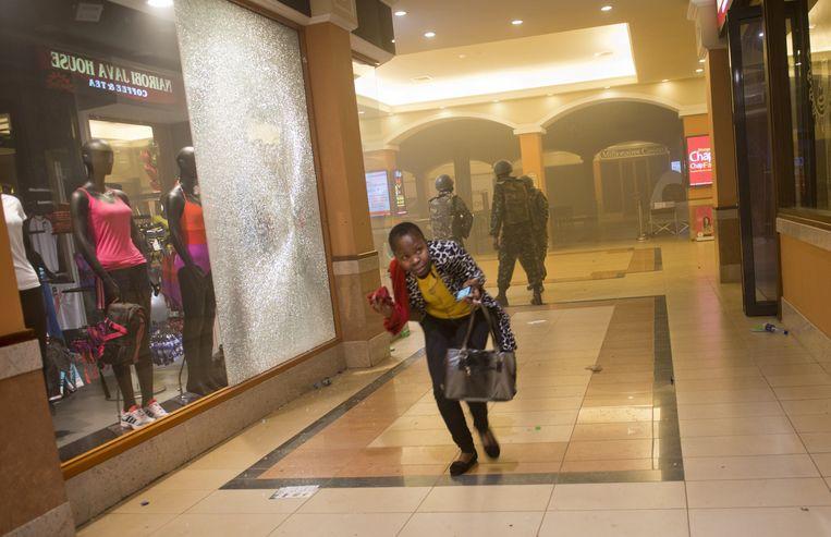Een vrouw vlucht voor het geweld van Al-Shabaab in winkelcentrum Westgate in de Keniaanse hoofdstad Nairobi. Beeld AP/Jonathan Kalan