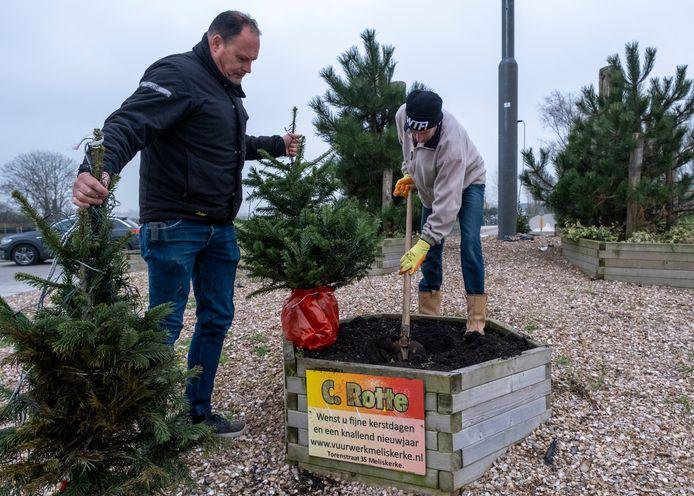 Carlo Rotte (l) met een in brand gestoken kerstboom; Michel van der Ree (r) plant een nieuwe.