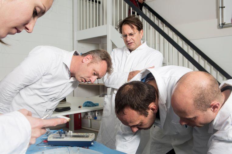 Hart-longchirurg Michiel Erasmus (met bril) test een varkenshart in het laboratorium van het Groningse bedrijf Organ Assist. Beeld Niels Blekemolen