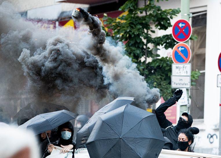 Enkele betogers, hier wel een mondmasker om niet herkend te worden, gooiden rookbommen naar de oproerpolitie.