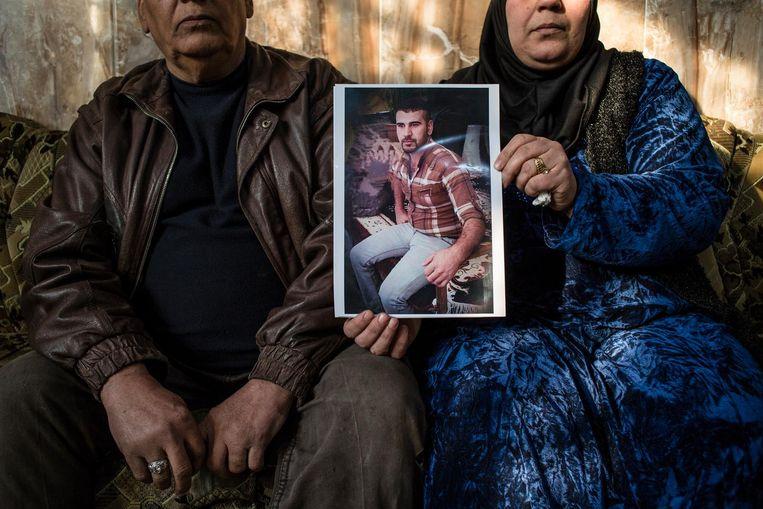 Ouders met een foto van hun zoon die omkwam tijdens een bombardement op IS in de buurt van hun woning. Beeld Hawre Khalid