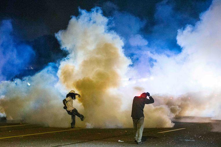 Een demonstrant trapt een traangasgranaat terug naar de politie. Beeld reuters