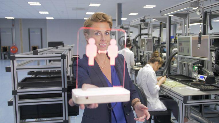 Janneke van den Heuvel, ceo van het Amsterdamse bedrijf TryLikes toont de Aura Aware, een schermpje met sensor dat rood oplicht als iemand een balie of koffiebar te dicht nadert. Beeld Aura Aware