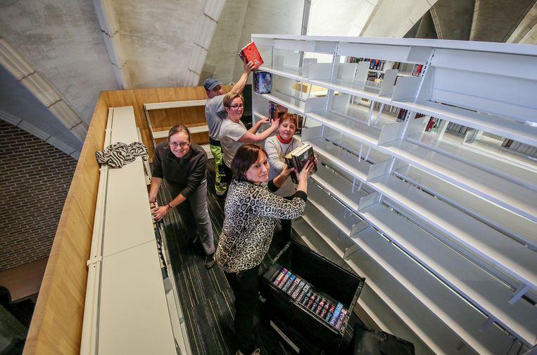 Nico Goemaere van de technische dienst en Nele Verfaille, Lien Ceenaeme, Bianca Wijns en Kathleen Verrhue van de bib vullen de boekenrekken van de nieuwe bibliotheek in de kerk van Wielsbeke.