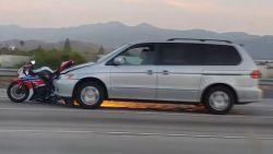Auto scheurt met motorfiets op motorkap over snelweg