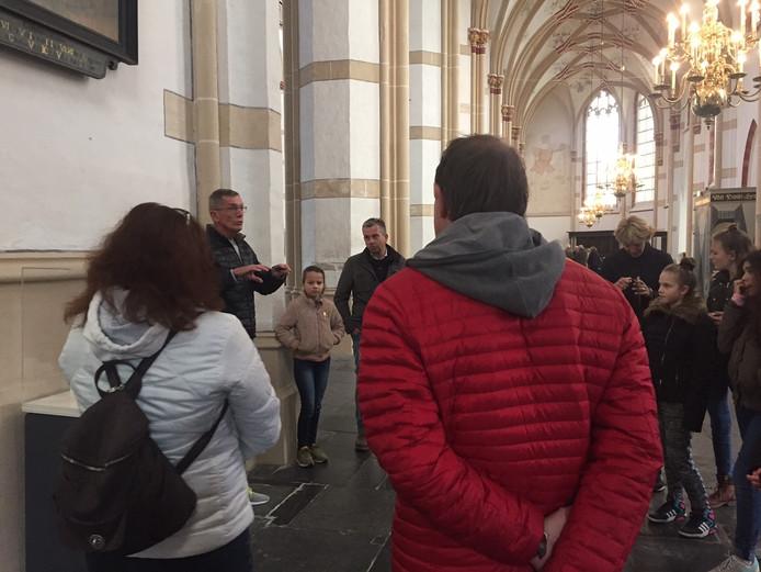 Gids Rein van Willigen begeleidt een groepje mensen door de kerk.