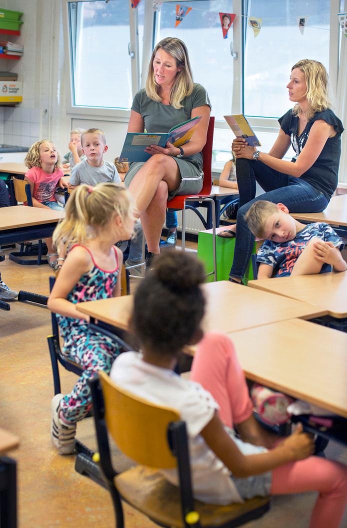 Op de koningin Julianaschool in De Lier geven moeders Esther (links) en Anne Marie een alternatieve les voor de klas door voor te lezen.